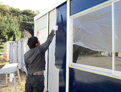 ユニットハウスを塗装するスタッフ